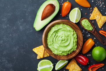 Bowl guacamole with avocado, lime and nachos top view. Mexican food.