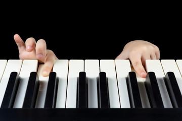 Children's fingers press the piano keys
