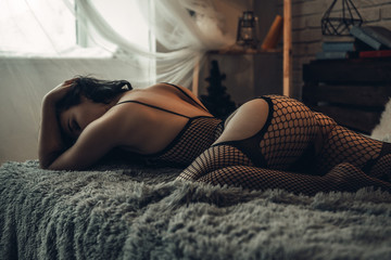 Fashion art photo of sensual woman in bedroom. Home interior. Evening