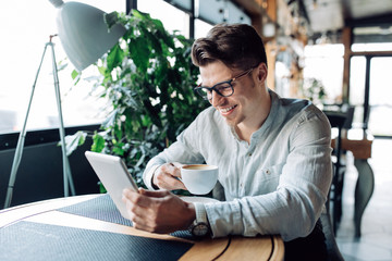Cheerful attractive man sitting at cafe with netbook, watching a movie, drinking coffee, wearing eyeglasses. Enjoying leisure time.