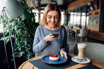 Cheerful nicegirl taking photo of tasty cake on mobile phone, spending time at cafe with cup of latte. Dressed in sweater.