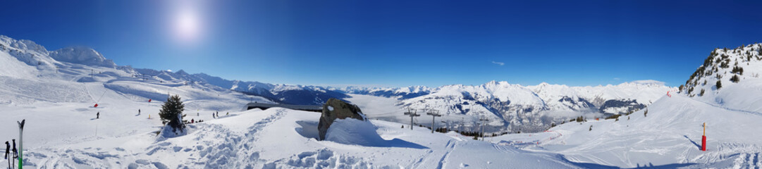 beautiful panoramic landscape on the slopes in  the snowy mountain under sunny blue sky
