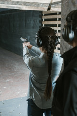 rear view of girl shooting with gun in shooting range