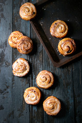 Homemade glazed puff pastry cinnamon rolls with custard and raisins on oven tray over old dark blue wooden background. Top view, space. Rustic style