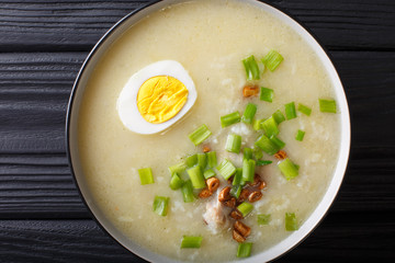 Homemade Asian rice soup with chicken, vegetables and egg close-up. horizontal top view