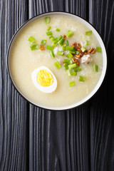 Homemade Asian rice soup with chicken, vegetables and egg close-up. vertical top view