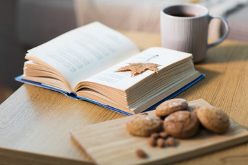 Fototapete - book with autumn leaf, cookies and tea on table