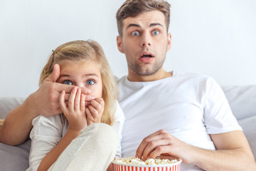 scared father and daughter watching horror movie at home