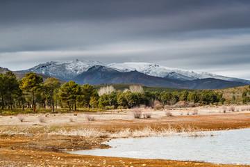 Embalse de Tabuyo del Monte, bosque de pinos y macizo del Teleno nevado.