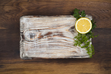 Old cutting board with lemon and herbs on wooden background
