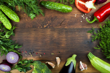 Raw vegetables on wooden texture background with copyspace in center
