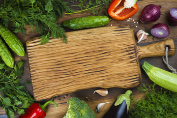 Vegetables on wooden texture background around cutting board in center