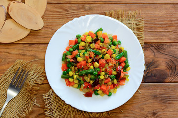 Vegan winter vegetable stew on a serving plate and wooden table. Home stewed carrots, green beans, red beans, peas, corn, pepper and onions. Healthy vegan stew recipe. Top view