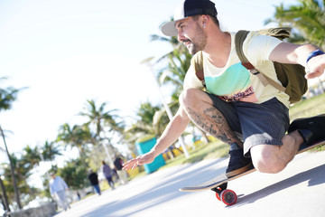 Trendy guy riding skateboard in Miami South Beach promenade