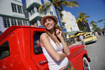 Model standing near red old-fashioned truck