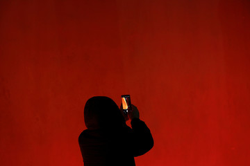 A man takes pictures of the super blue moon above the Forbidden City in Beijing