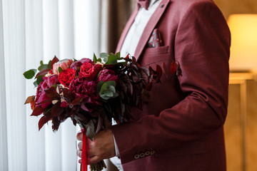 Groom in stylish red suit holding in his hands wedding bridal bouquet of red, white, pink flowers and greenery, with a ribbon of color Marsala