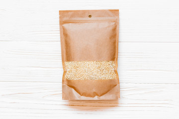 Mockup paper bag with quinoa seeds on white wooden table. Concept of a healthy diet. Super food.