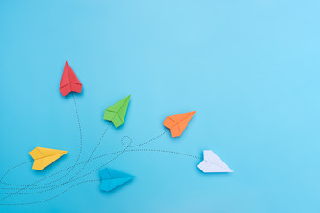Color paper airplanes on blue background.