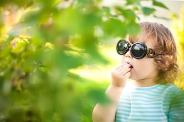 Cute toddler girl eats honeysuckle outdoors.