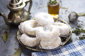 Oriental Algerian sweet cookies( kaab el ghazal), tea cup and pot  and mint leaves