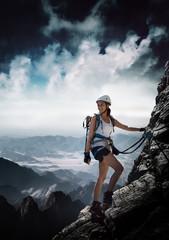 Frau klettert an einem Klettersteig (Via Ferrata)