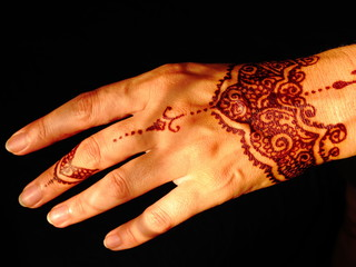 Woman's hand with traditional menhdi henna ornament on dark blue background