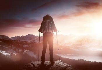 Bergsteiger steht auf Gipfel bei Sonnenaufgang