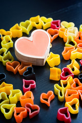 Heart-shaped pasta on black table