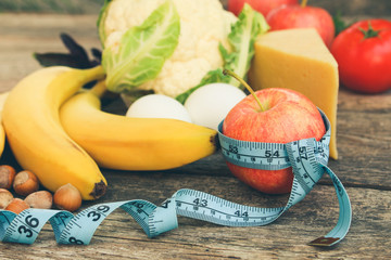 Fruits and vegetables, tape measure on old wooden background. Concept of proper nutrition. Toned image.