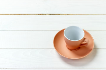 empty colourful cup on plate for coffee or tea on wood background