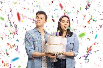 Teenagers with a birthday cake and party horns