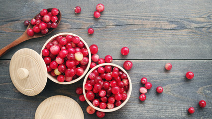 Fresh juicy cranberry in wooden round bowls with a wooden spoon on a table, close up