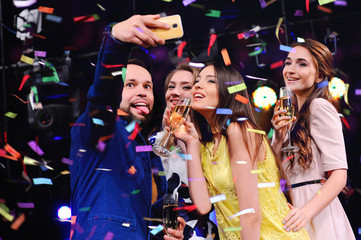 the cheerful company of best friends taking a selfie on your camera phone. To take a photo of yourself. Party, holiday, night club.