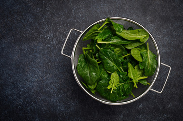 Fresh green spinach leaves on a dark concrete background, top view, flat lay, copy space.