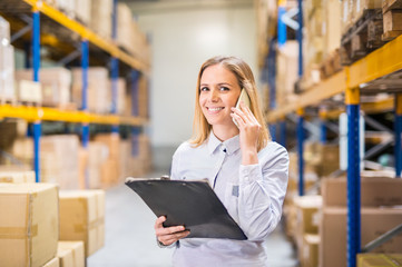 Woman warehouse worker or supervisor with smartphone.