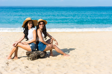 Lesbian couples or close friends are sitting on the beach While relaxing vacation or weekend on sunny days and nice weather in travel and holiday concept.