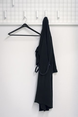 a black bathrobe is hanging at the wardrobe