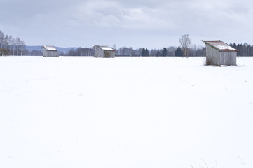 a snow covered landscape with three huts