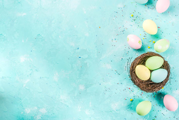 Multicolored Easter eggs with decorative bird's nest and sugar sprinkles on a light blue background,copy space
