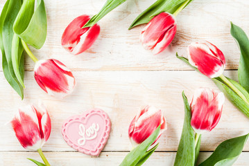 Valentines day background for congratulations, greeting cards. Fresh spring tulips flowers with pink chocolate candy, on white wooden background top view copy space frame