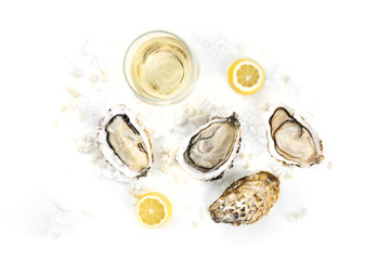 Overhead photo of three oysters with wine, lemon, and copy space