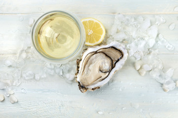 An overhead photo of an oyster with wine and lemon
