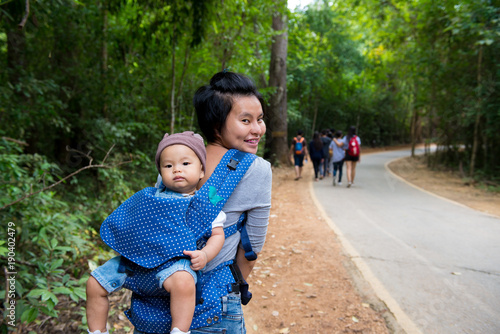 Mother Hold Baby Girl 10 Months On Back In Baby Carrier Walking In