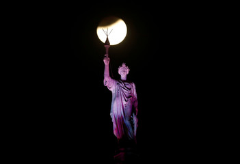 """A lunar eclipse of a full """"Blue Moon"""" is seen above a statue at the Chhatrapati Shivaji Terminus railway station in Mumbai"""