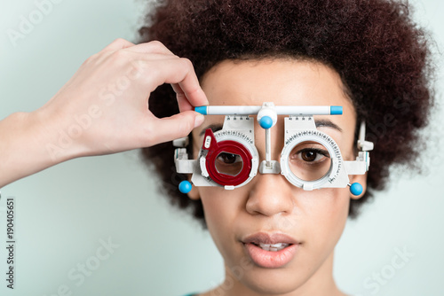 d407d946da Woman having eyesight test with phoropter for new glasses at optician or  eye doctor specialist