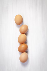 the Five yellow eggs lie in a line on a white wooden table