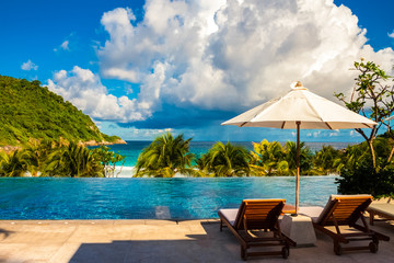 A great holiday image of two deck chairs next to each other, shaded by a patio umbrella in between and in front is a wonderful view of an infinity pool and the beach.
