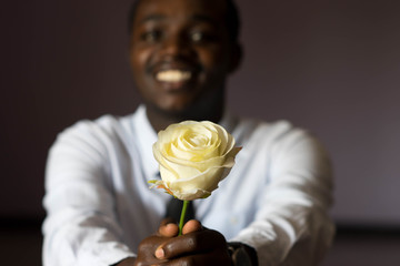 African man holding white rose.Low key style.