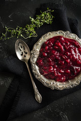 Cranberries with Orange Sauce Served in an Antique Silver Bowl Accompanies by Thyme